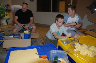 Boys hard at work filling lanterns with batteries and making paper flowers for the upcoming Colour conference.
